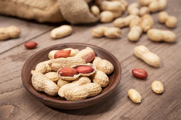 Amendoim em tigela na mesa de madeira rústica. arachis hypogaea