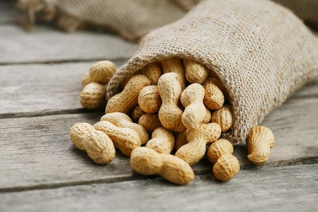 Amendoim em um saco de aniagem em miniatura na superfície de madeira velha e cinza