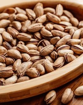 Amendoim fresco com sal e saboroso salgadinho de amendoim na mesa, vista de frente fechada