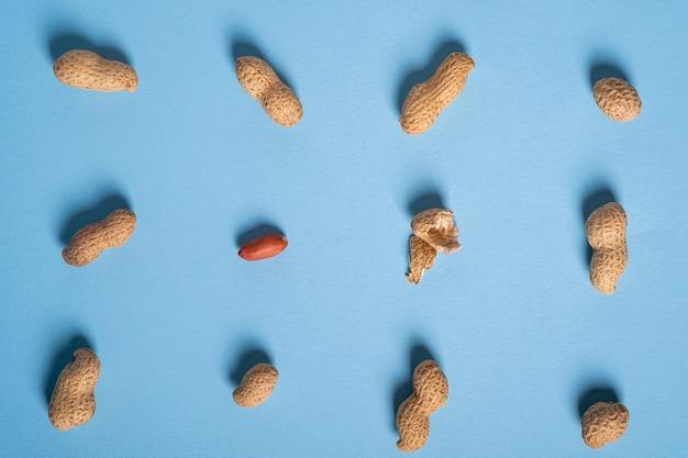 Amendoim liso leigos mínimo no padrão de comida de mesa azul, textura de noz, vista superior