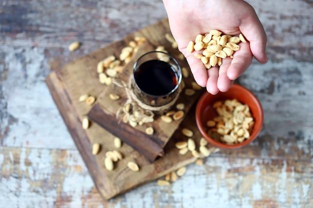 Amendoim na mão e refrigerante preto com amendoim.