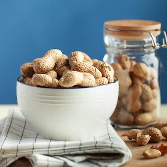 Amendoim sem casca em uma tigela sobre um pano de prato o conceito de uma dieta saudável um lanche para vegetarianos ...