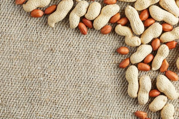 Amendoim torrado com casca e descascado em um tecido marrom.