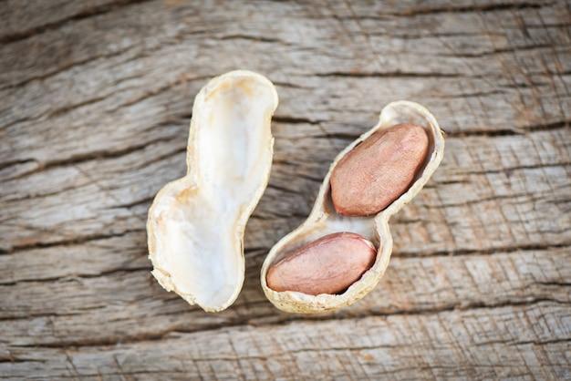 Amendoim torrado em um fundo de madeira - amendoim com casca em conchas para alimentos ou lanche