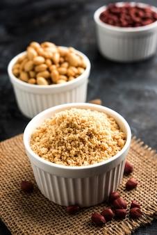 Amendoim triturado ou pó de mungfali com amendoim inteiro torrado. servido em uma tigela sobre um fundo mal-humorado. foco seletivo
