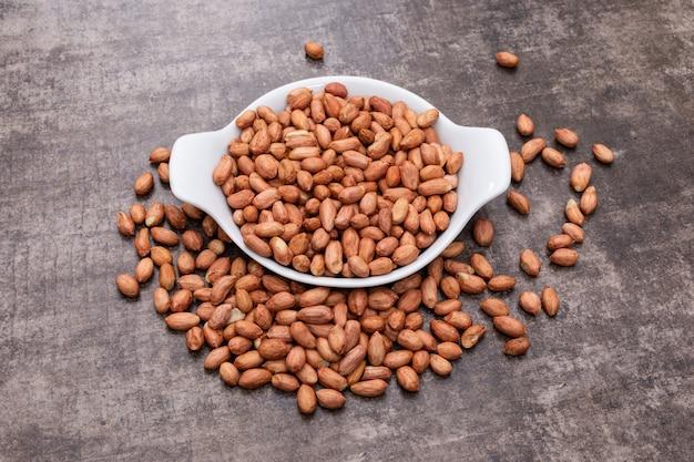 Amendoins de alto ângulo vista na tigela na pedra horizontal