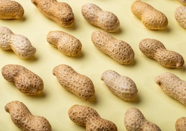 Amendoins de vista lateral próxima com casca em um fundo amarelo