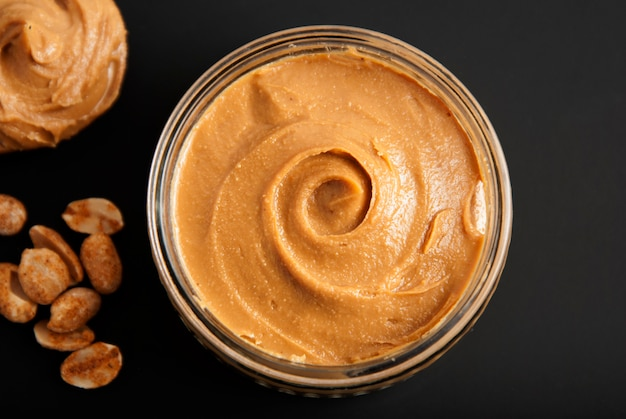 Amendoins e manteiga de amendoim fresca, fundo preto.