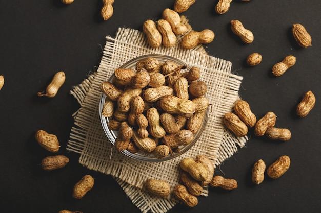 Amendoins em tigela sobre o fundo escuro.