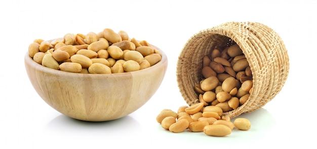 Amendoins na cesta e tigela de madeira no fundo branco