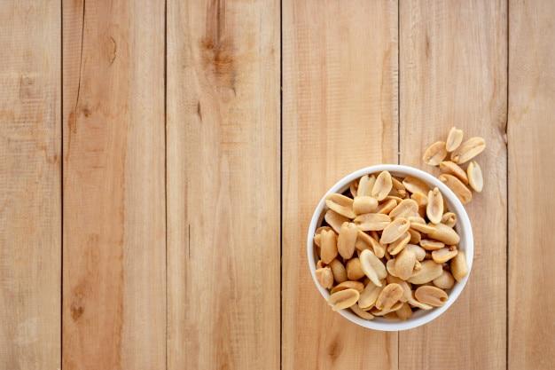 Amendoins salgados assados em uma tigela de cerâmica no fundo de madeira