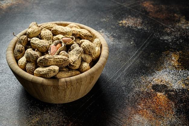Amendoins sem casca crus na casca. amendoim orgânico. fundo preto. a vista do topo. espaço para texto