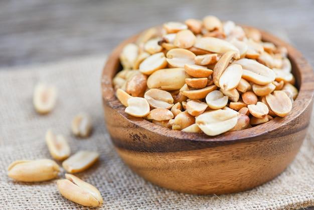 Amendoins torrados em uma tigela de madeira e saco - amendoins salgados como um alimento ou lanche