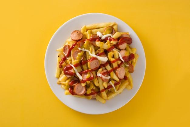 América latina típica salchipapa na superfície amarela. salsichas com batatas fritas, ketchup, maionese e mostarda.