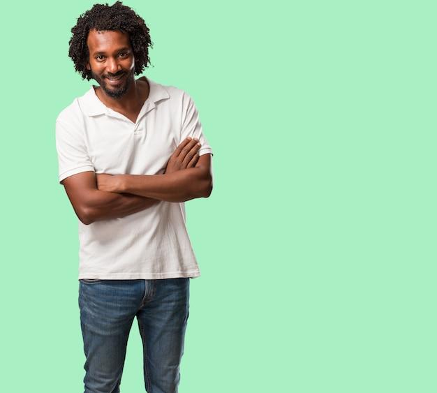 Americano africano considerável que cruza seus braços, sorrindo e felizes