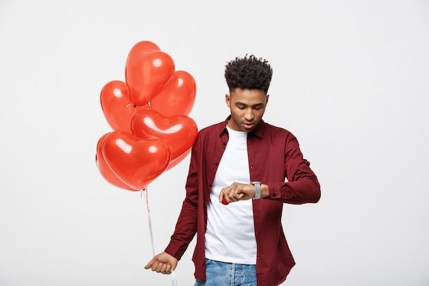 Americano africano considerável que guarda o balão do coração e que verifica o tempo em seu relógio.