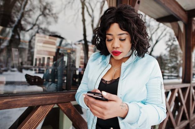 Americano africano elegante mais o modelo do tamanho com o telefone celular à mão contra o café de madeira no dia de inverno.