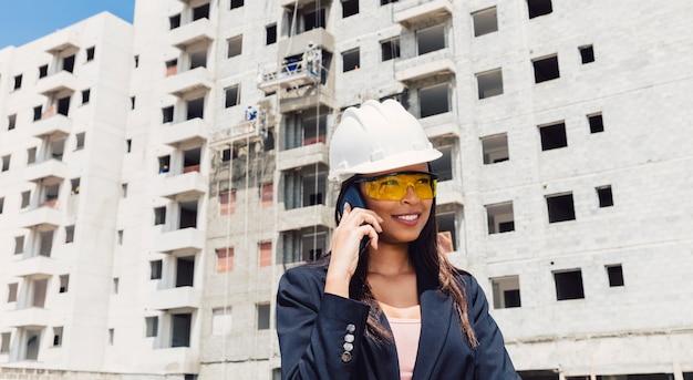 Americano africano, senhora, em, capacete segurança, falando, ligado, smartphone, perto, predios, construção