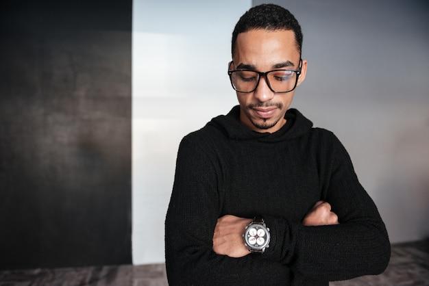 Americano africano sério jovem olhando para relógio de pulso