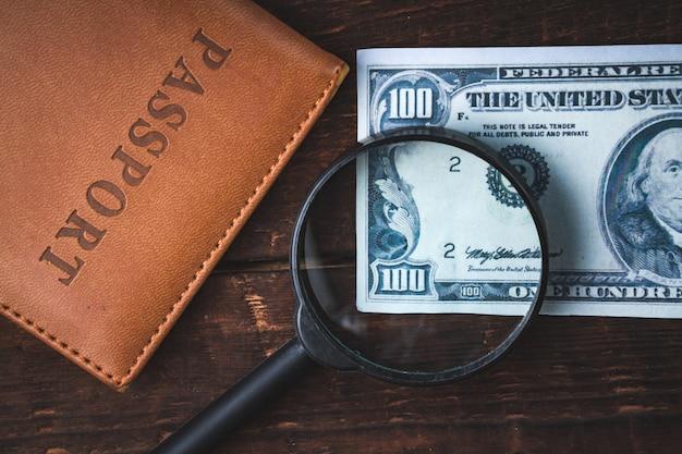 Americano cem dólares, passaporte e lupa sobre uma mesa de madeira. conceito de dinheiro, conceito financeiro.