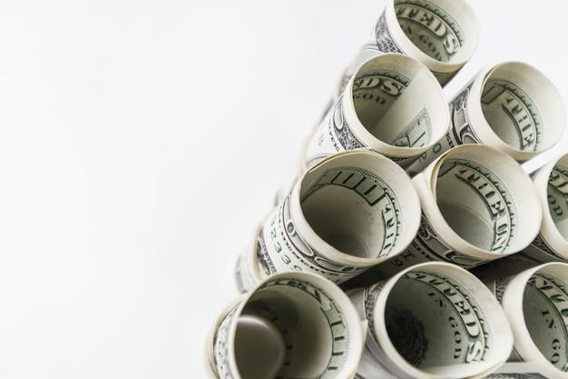 Americano cem notas de dólar roladas e empilhadas em uma pirâmide.