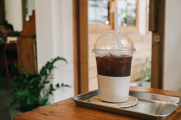 Americano de gelo americano em copo na mesa de madeira no café.
