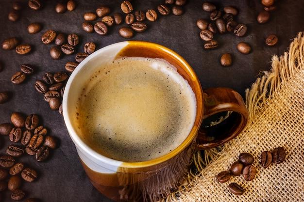 Americano na caneca branca e marrom em um escuro. serapilheira fica nas proximidades, grãos de café estão espalhados