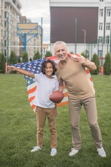 Americanos. menino de cabelos escuros em uma camiseta branca e seu pai com uma bandeira