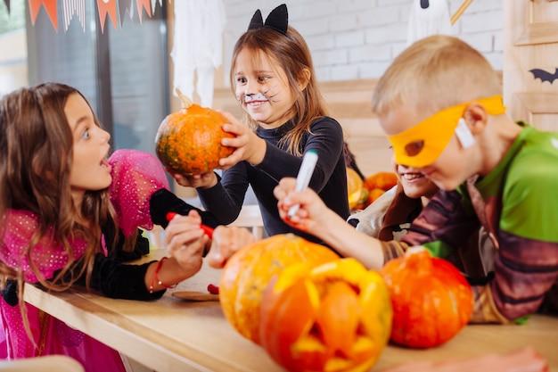 Amiga assustadora. linda garota de cabelos escuros com cara de gato pintada assustando seus amigos comemorando o halloween juntos