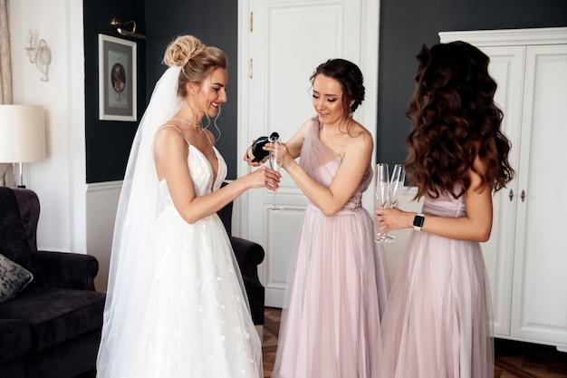 Amiga da noiva está derramando o champanhe para a noiva e outra mulher