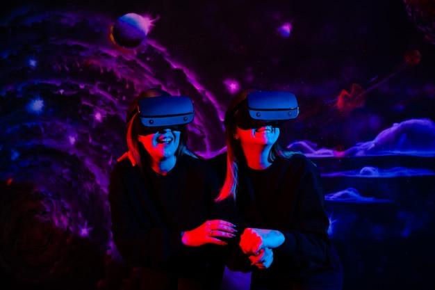 Amiga de duas irmãs com óculos virtuais de mãos dadas se divertindo na sala de jogos em luz neon azul e vermelha
