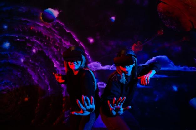 Amiga de duas irmãs jovens com óculos virtuais se divertindo em foto de alta qualidade de luz neon azul e vermelha