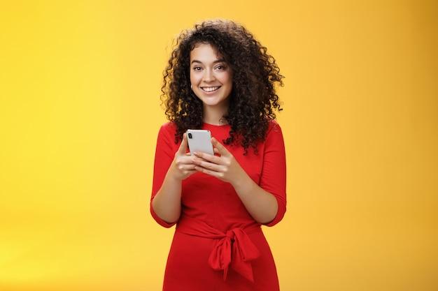 Amiga de mensagens de menina para contar todos os boatos quentes segurando o telefone celular nas mãos, sorrindo amplamente e entusiasmo ...