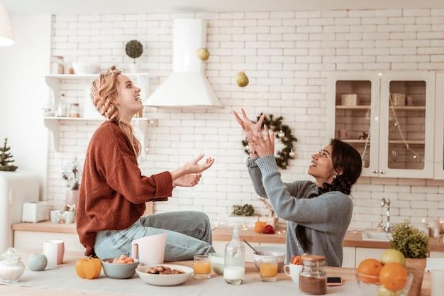 Amiga loira brincalhona. garotas adultas infantis jogando pequenas maçãs para o alto enquanto estão de bom humor pela manhã