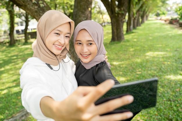 Amiga muçulmana tirando selfie ou fazendo videochamadas ao ar livre usando seu smartphone durante o esporte
