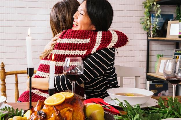 Amigas abraçando no jantar de natal