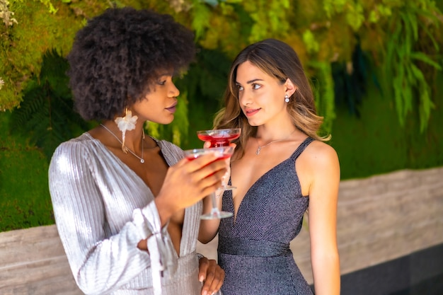 Amigas afro-americanas e brancas usando vestidos elegantes, bebendo vinho e conversando