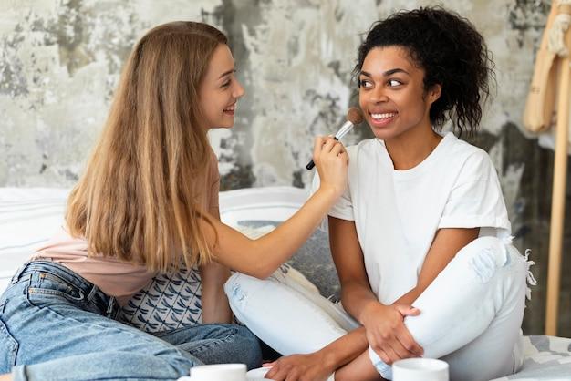 Amigas ajudando umas às outras com maquiagem na cama