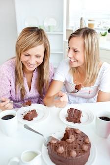 Amigas alegres comendo um bolo de chocolate na cozinha