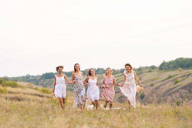 Amigas alegres se divertem juntos em um piquenique em um lugar pitoresco com vista para as colinas verdes. mulheres em vestidos brancos dançando no campo