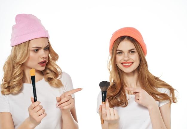 Amigas alegres usando chapéus com luz de fundo de amizade de cosméticos