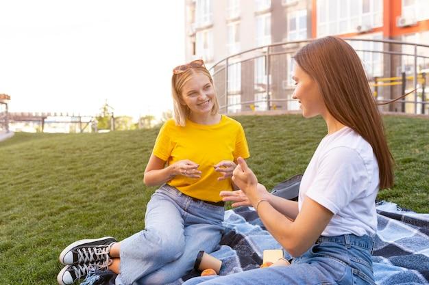 Amigas ao ar livre usando linguagem de sinais