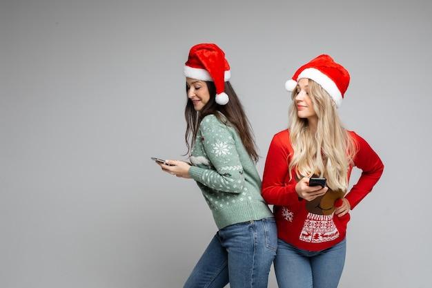 Amigas atrativas com chapéus de natal vermelho e branco e telefones