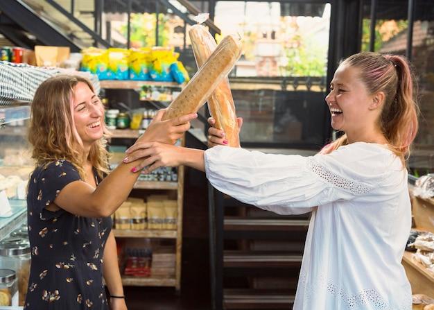 Amigas brigando com baguetes de pão
