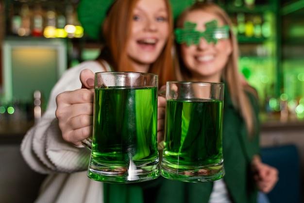 Amigas celebrando st. dia de patrick com bebidas no bar
