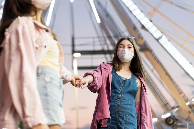 Amigas com máscaras médicas no parque de diversões