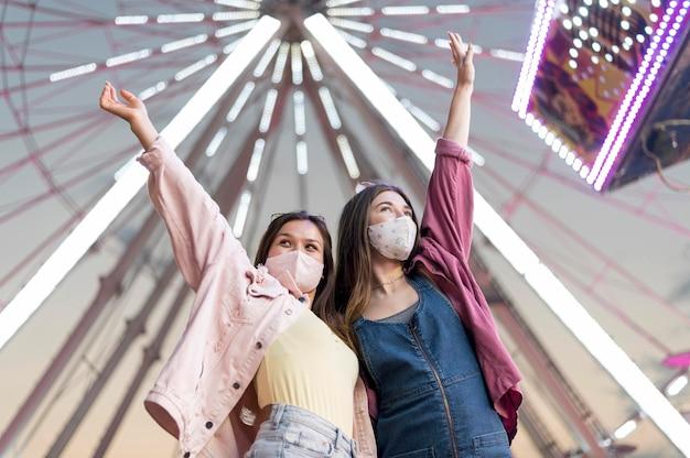 Amigas com máscaras no parque de diversões