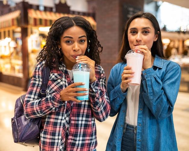 Amigas com milkshakes saindo juntas