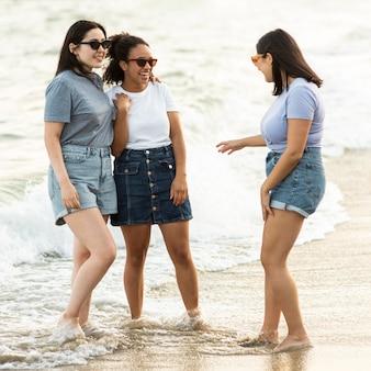 Amigas com óculos de sol juntas na praia