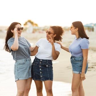 Amigas com óculos de sol na praia